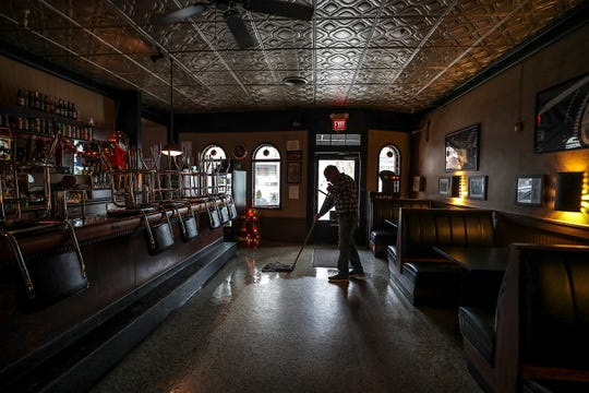 Rick Wessling mops the floor at Barret Bar. Wessling began mopping the floor of the bar at age six when his father owned it.