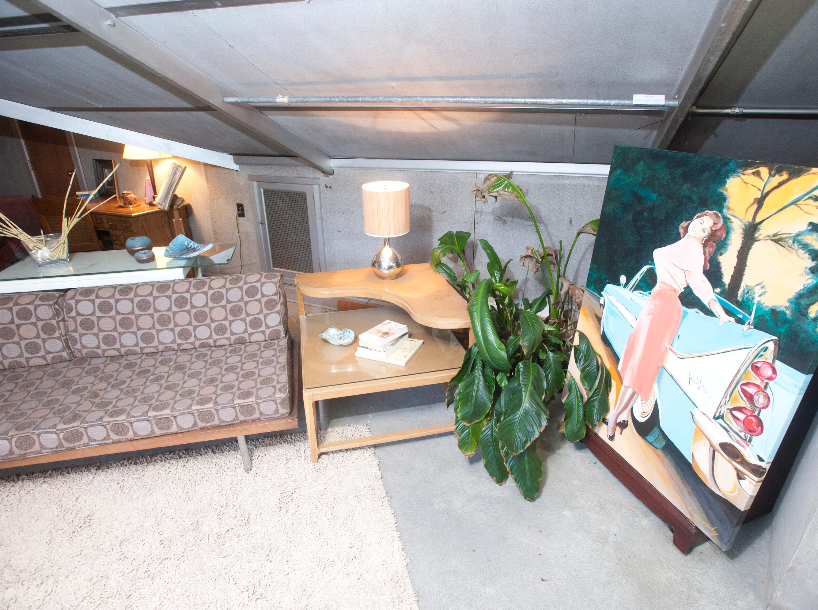 """The home's attic has been converted to livable space where Cannady has his artist studio and a spare bed. At right is Cannady's painting, """"Miss Lube Rack.""""10 December 2018"""