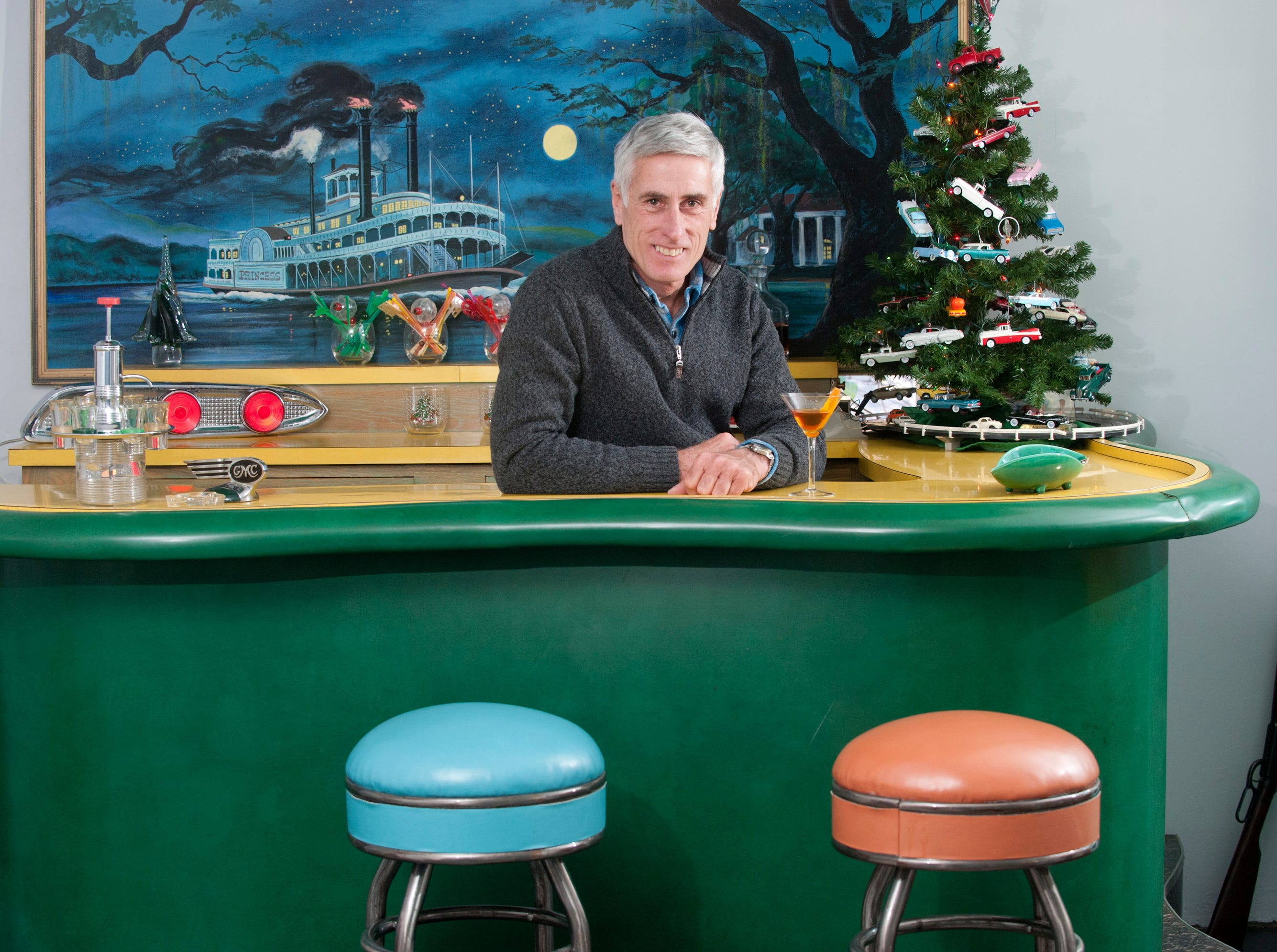"""Tom Cannady relaxes behind the second floor """"Princess"""" bar which was moved from the 1st floor. Behind Cannady is his painting of the riverboat Princess for which the bar is named, and at night is illuminated by blacklight. During the day, the painting fits into a pocket below it revealing a window.10 December 2018"""