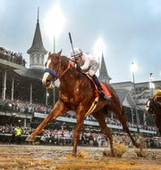 Finish line lights illuminate Justify, and jockey Mike Smith as they cross the finish line at Churchill Downs in a driving rain to win the 144th running of the Kentucky Derby and the first leg of the Triple Crown.