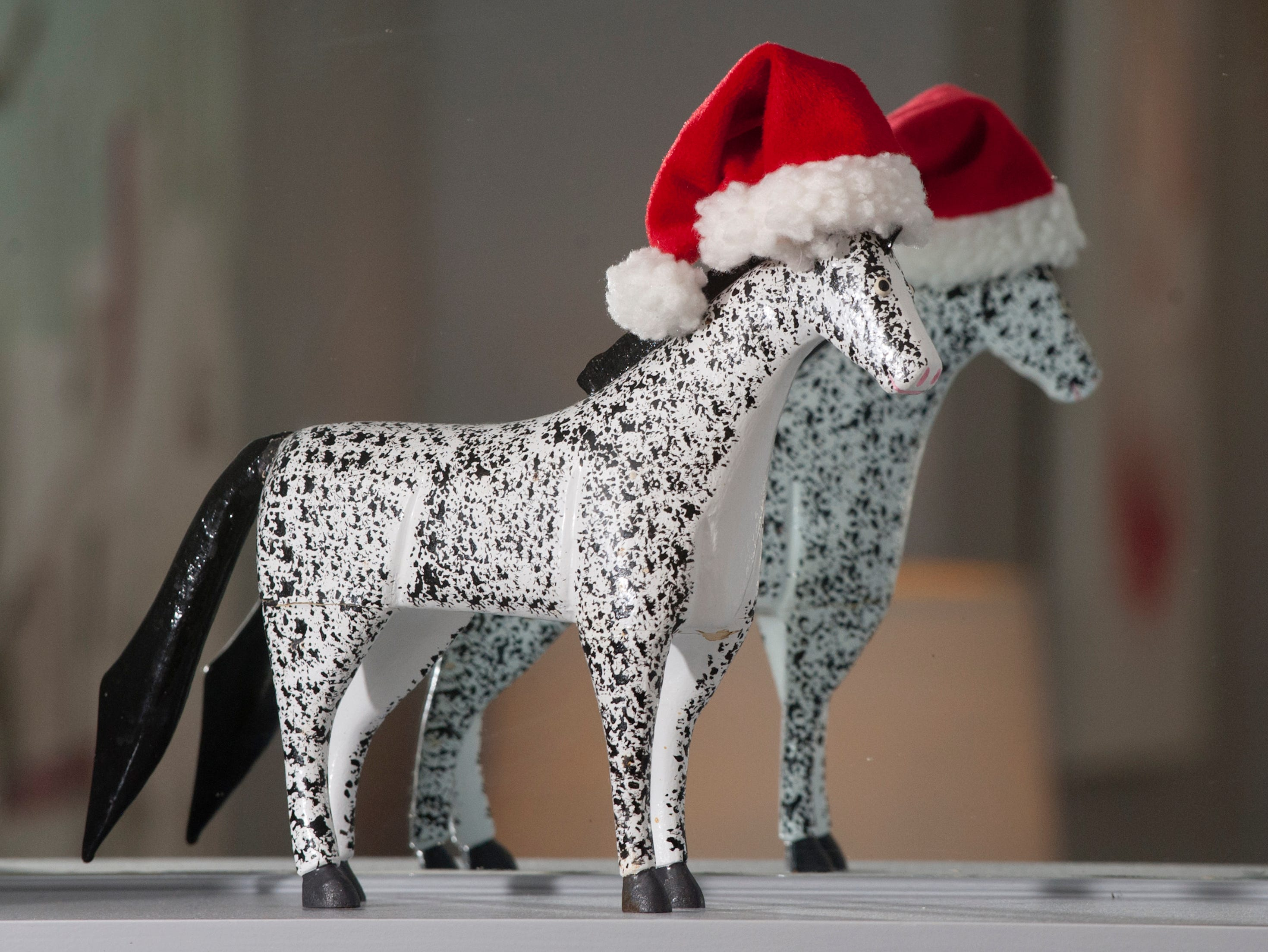 A horse made by Kentucky folk artists Lonnie and Twyla Money, is decorated with a small Santa had and sits on the shelf of the home's dining room. 10 December 2018