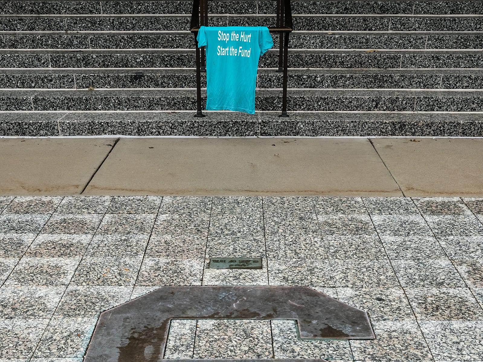A teal colored t-shirt is placed in front of the MSU Administration Building after a MSU Board of Trustees meeting Friday, Dec. 14, 2018. Nassar survivors and supporters want the Board to reinstate the fund to survivors.