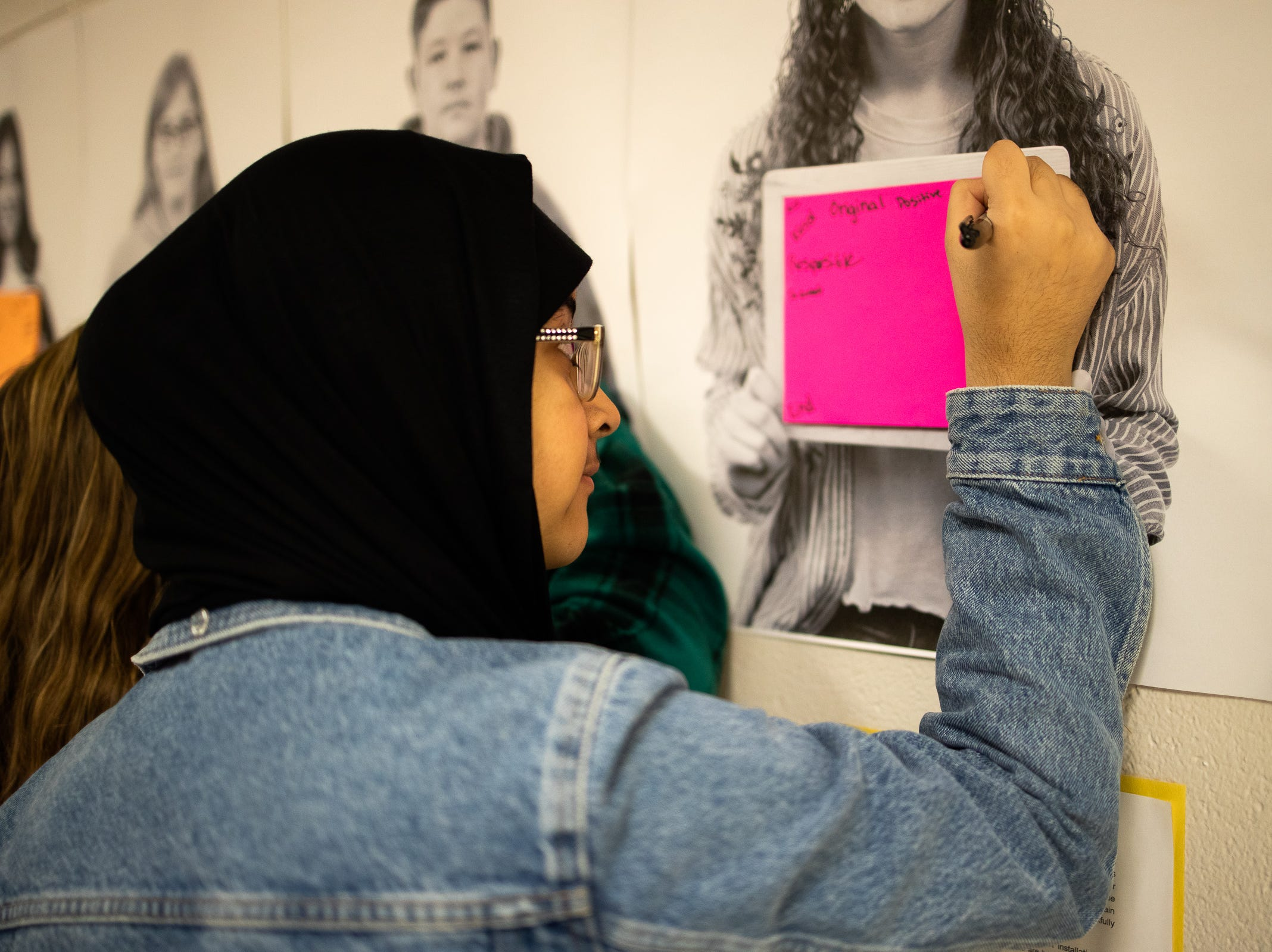Seba Aldhamen, 16, write words of encouragement on every student's photograph in the hallways of Bath High School.
