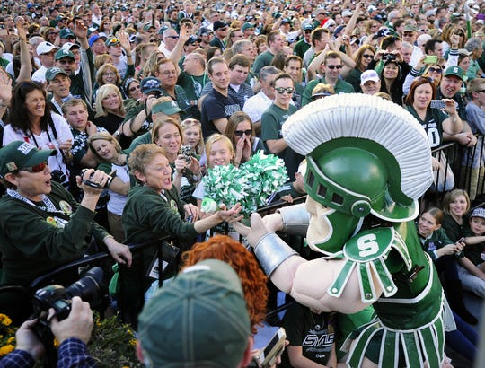 MSU mascot Sparty hands a green rose to MSU alum Joyce Jilg as 27,000 Spartan fans gather at a Rose Bowl pep rally in downtown Los Angeles on Dec. 31, 2013. More than years later, MSU fans long for a similar buzz.
