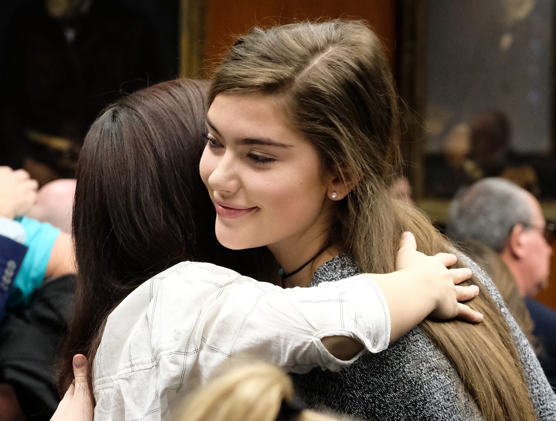 Emma Ann Miller, right, embraces Kaylee Lorincz at a MSU Board of Trustees meeting Friday, Dec. 14, 2018. The two survivors of Larry Nassar expressed their displeasure at the Board for cancelling the Healing Assistance Fund set up for survivors to access treatment.