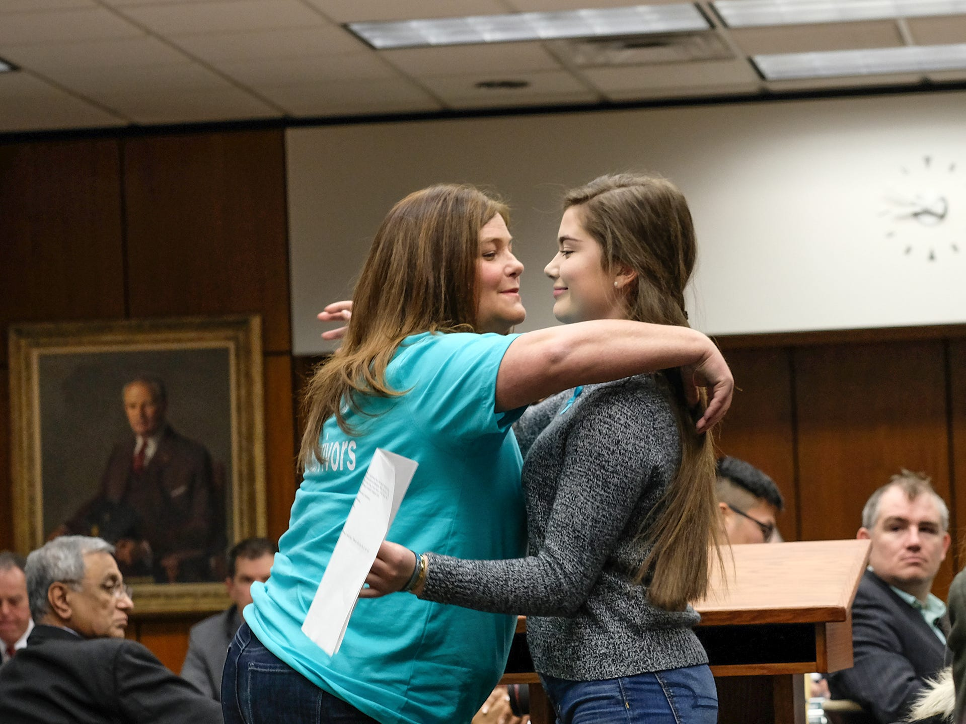 After speaking, Leslie Miller, left, and her daughter Emma Ann Miller embrace at the MSU Board of Trustees meeting Friday, Dec. 14, 2018.The mother and daughter were critical of the Board for cancelling the Healing Assistance Fund set up for victims of Larry Nassar.