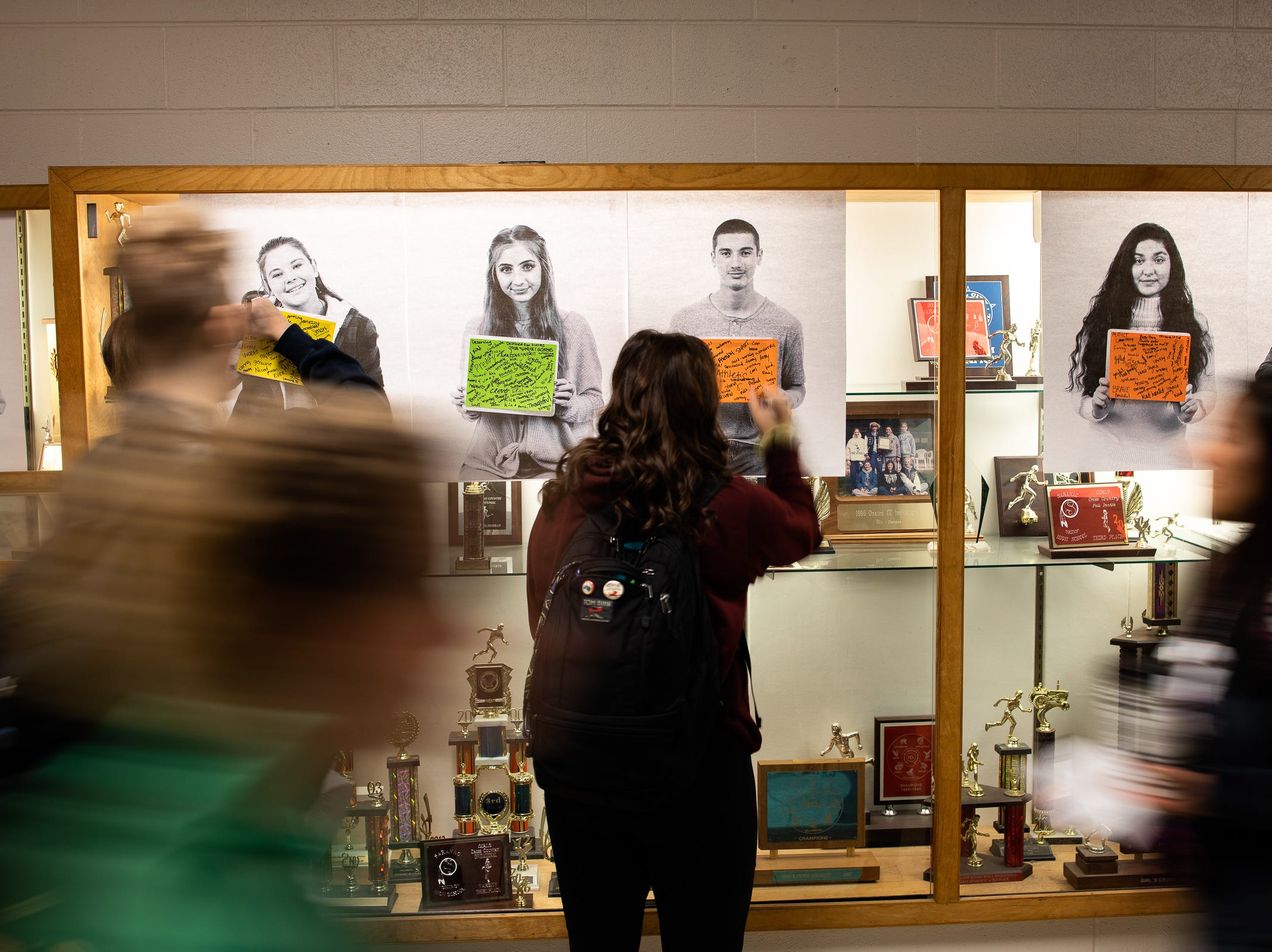 Bath High School students roam the halls, writing positive words and phrases on the photos of friends and fellow students.