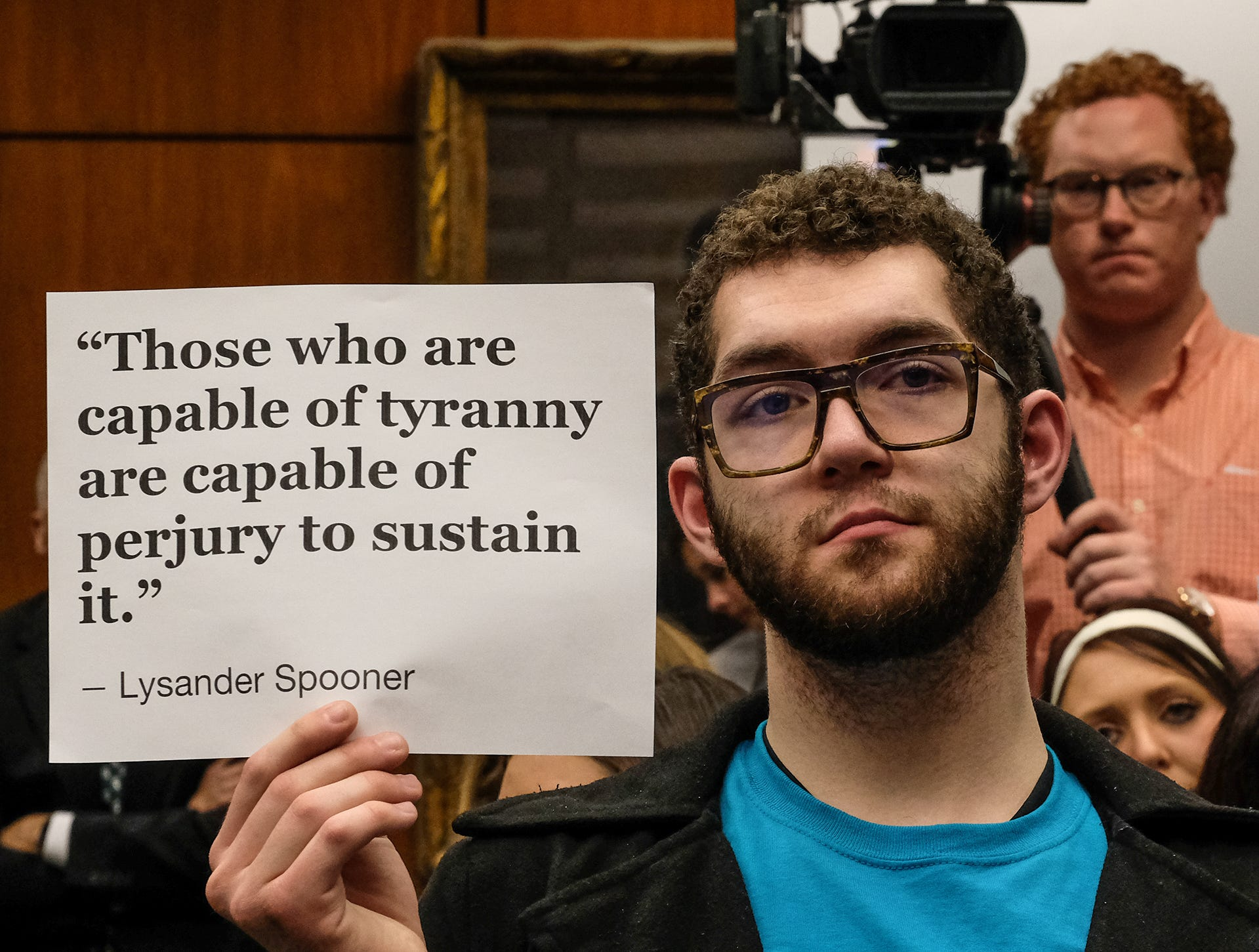 MSU student Colin Wiebrecht along with others in the audience hold up quotes they feel is pertinent to the proceedings at the MSU Board of Trustees meeting Friday, Dec. 14, 2018. Attendees were critical of the Board for cancelling the Healing Assistance Fund set up for victims of Larry Nassar.