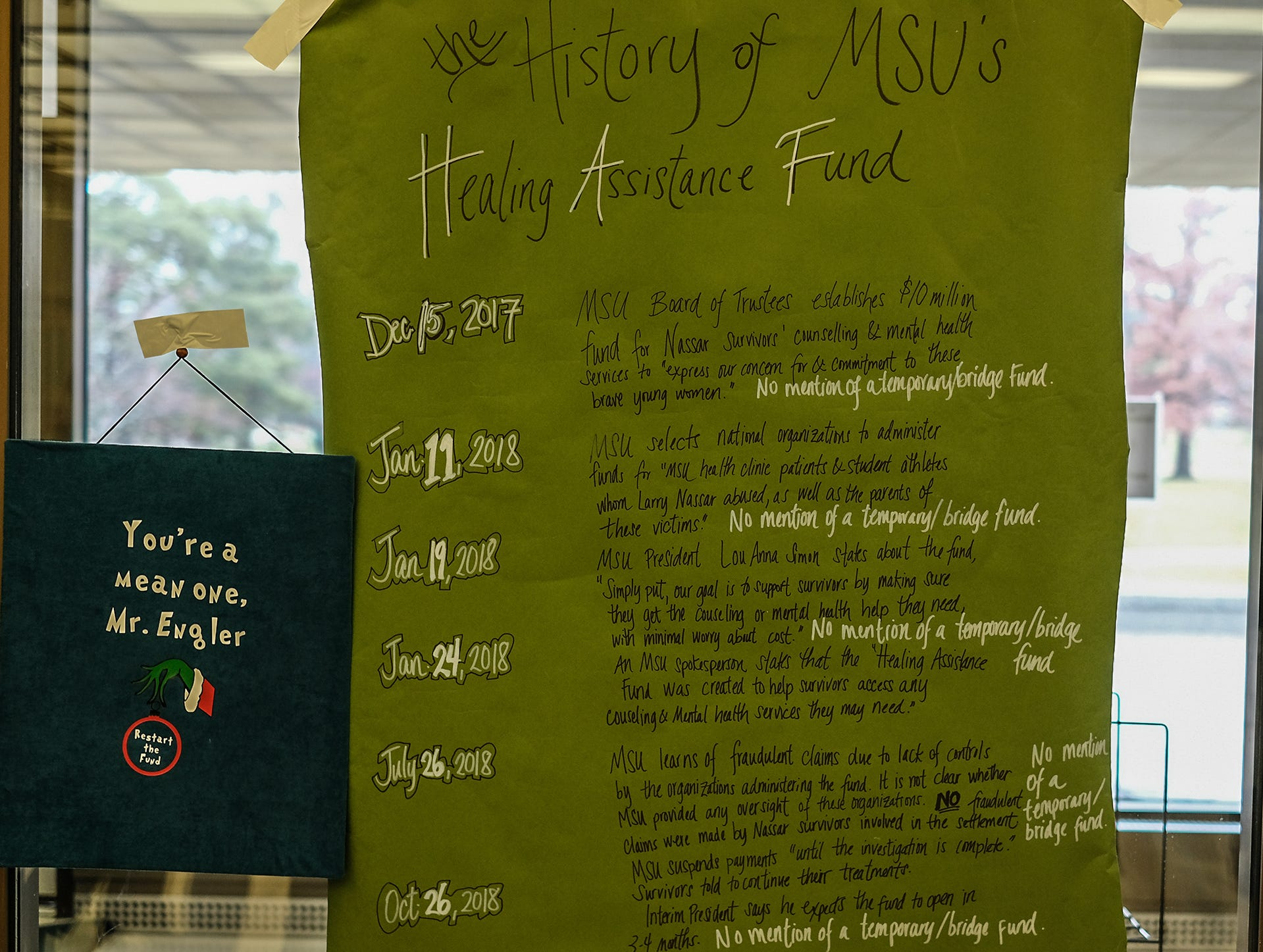 A sign is posted in the window of the MSU Administration Building expressing displeasure at the cancelling of the Healing Assistance Fund set up for victims of Larry Nassar. Friday, Dec. 14, 2018.