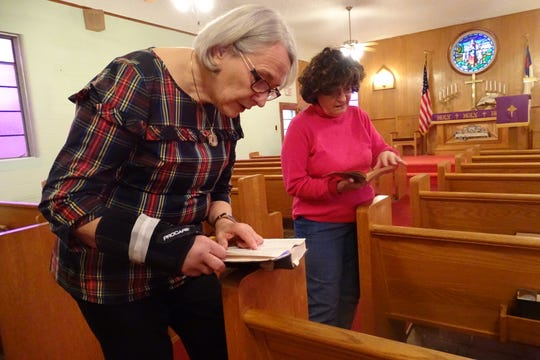 Elaine Siewert, left, and Erna Clark look over German hymnals inside St. Peter's Evangelical Lutheran Church.