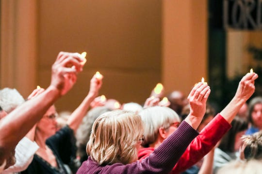 December 13, 2018 - Candles are held in the air during a vigil to commemorate gun violence victims in Memphis and to mark the sixth anniversary of the Sandy Hook Elementary School shooting at First Congregational Church of Memphis. The First Congregational Church of Memphis and the Memphis chapter of Moms Demand action organized the vigil.