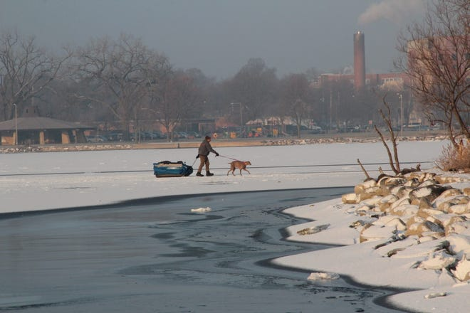 An ice fisherman and his dog walk on solid ice around an area of open water near shore on Lake Monona in Madison.