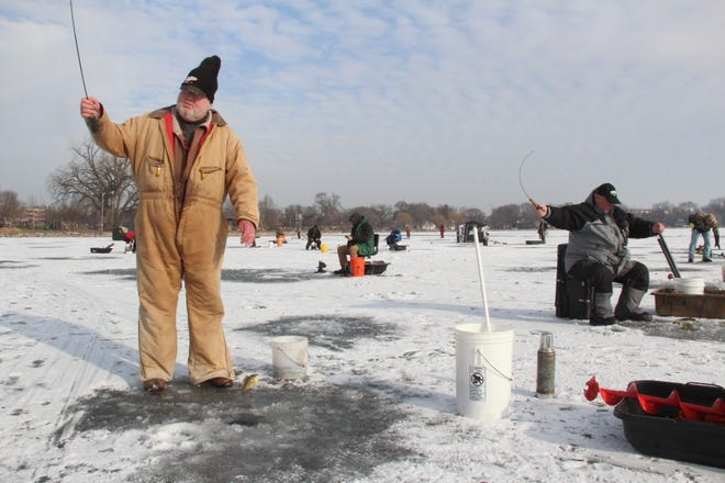 Mike Widen, left, of Mount Pleasant lifts a bluegill onto the ice while ice fishing on Lake Monona in Madison.