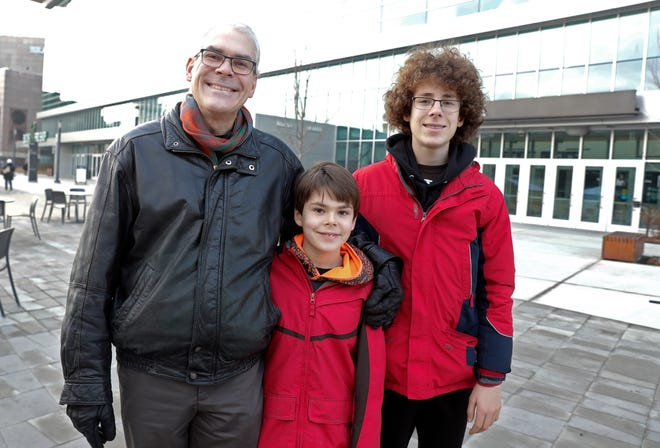 Steve Szymanski stands in front of Fiserv Forum with his two sons, Ryan (middle), and Tommy (older), who have been offered a chance to play the national anthem at an upcoming Bucks game. The boys get free tickets to the game, but Steve is upset that he and his wife must pay $66 each to watch their sons.