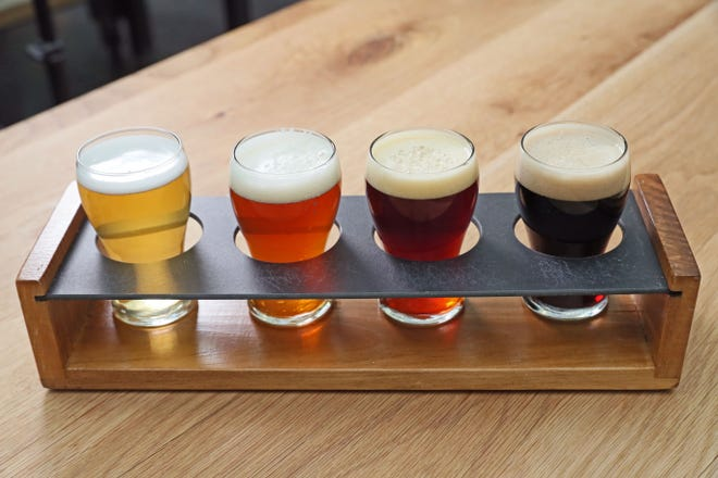 A flight of beer is prepared for customers.