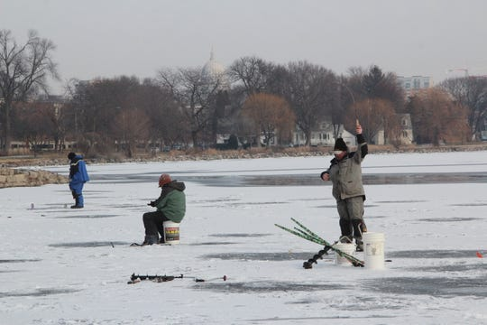 With the state capitol on the horizon, an angler sets the hook while ice fishing on Lake Monona.