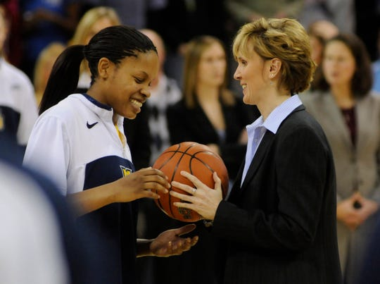 Former Marquette women's basketball coach Terri Mitchell salutes player Krystal Ellis in 2009 after Ellis became the program's all-time leading scorer.