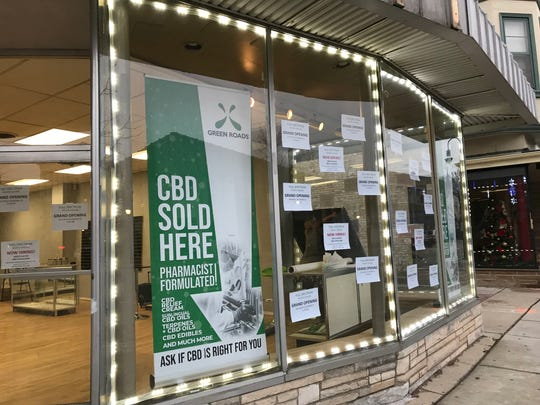 Michelle La Count (raising a panel on a side window) readies Waukesha's first CBD dispensary store, Full Spectrum Holistic Healing. The business plans to open a second location in Whitefish Bay.