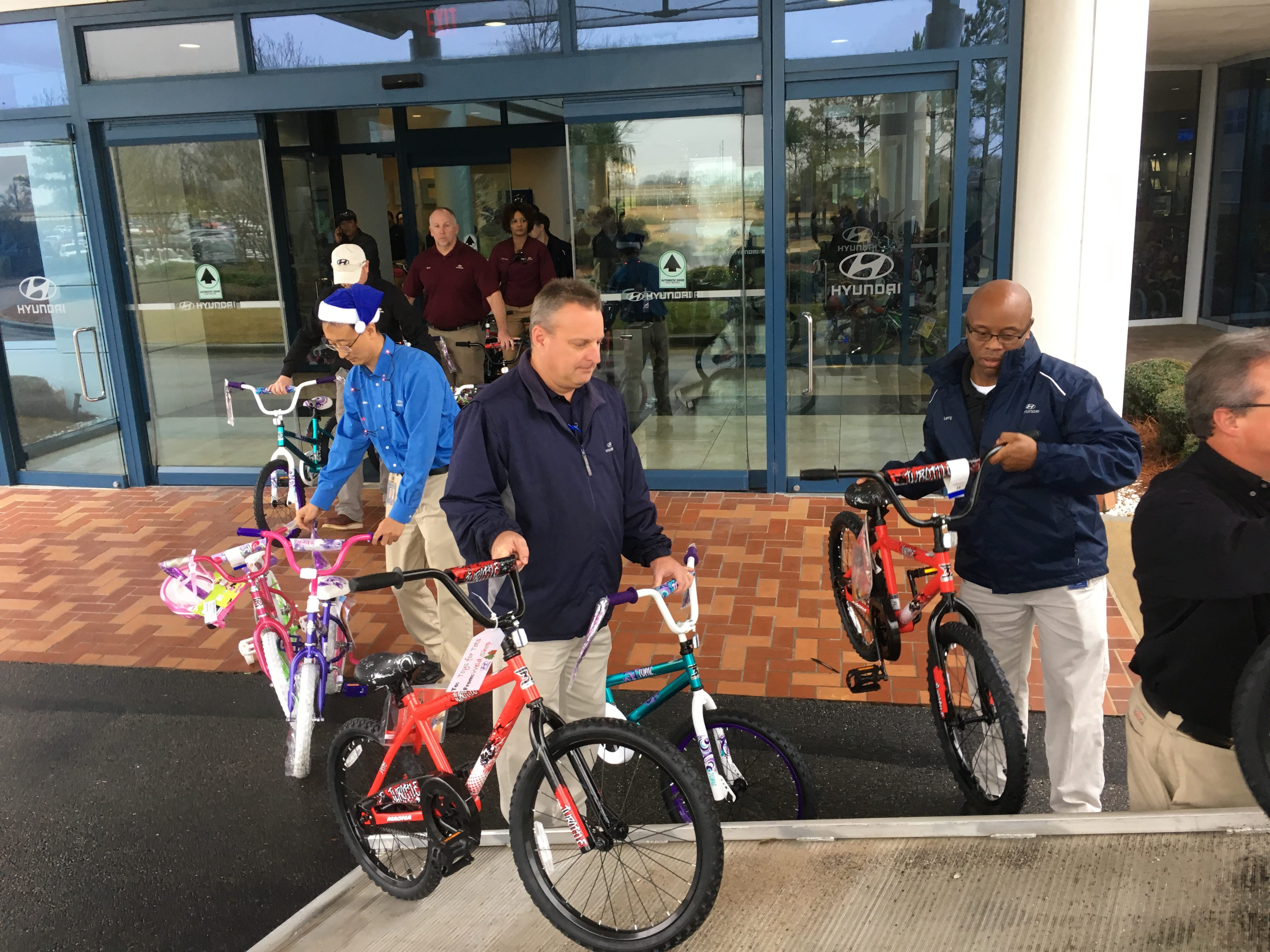 Workers at the Hyundai plant in Montgomery load donated bicycles into a truck.