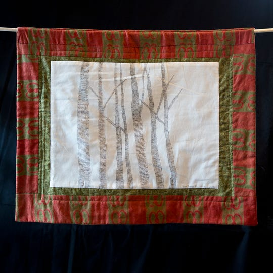 One of Lynda Tredway's quilts for Alabama. On the front, each pine needle represents one lynching victim, and the names are written on the back, as seen here.