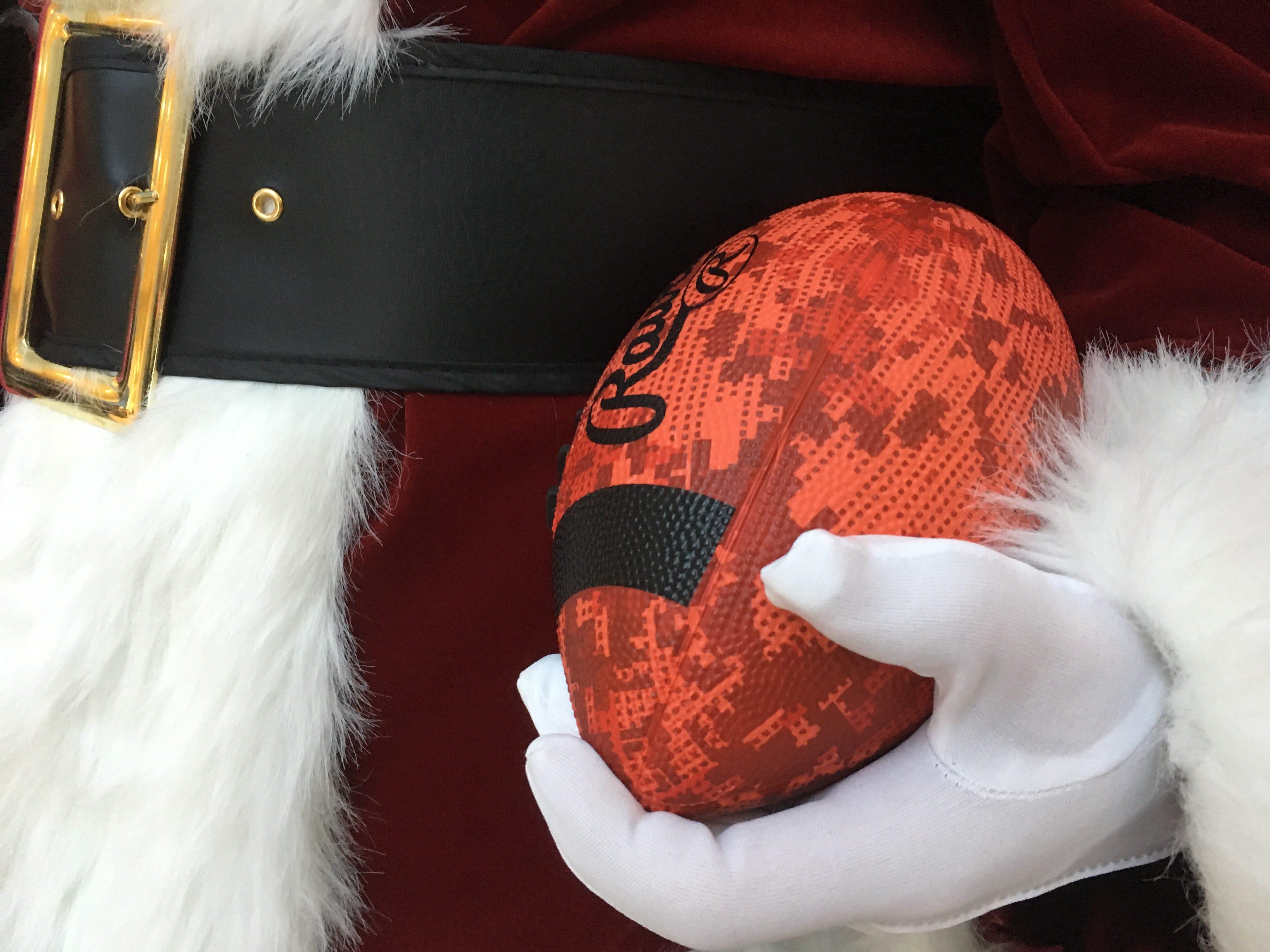 Santa holds a football during a toy donation at Hyundai Motor Manufacturing Alabama.