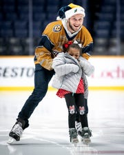 Nashville Predators defenseman Anthony Bitetto skates with Janavia Newsom, 4, during the West Nashville Dream Center Holiday Party at Bridgestone Arena in Nashville, Tenn., Wednesday, Dec. 12, 2018.