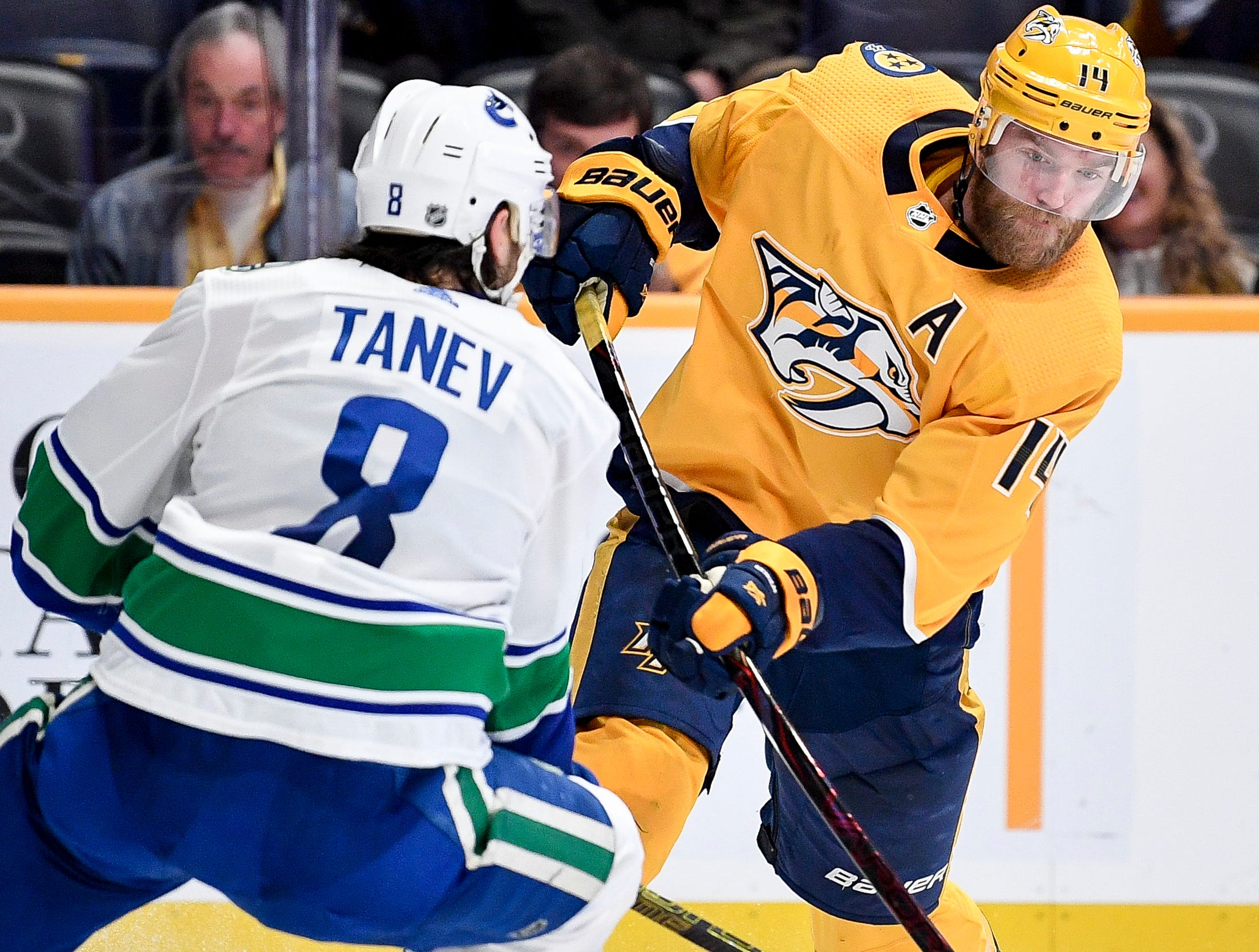 Dec 13: Predators 4, Canucks 3 (OT) -- Nashville Predators defenseman Mattias Ekholm (14) shoots past Vancouver Canucks defenseman Christopher Tanev (8) during the third period at Bridgestone Arena in Nashville, Tenn., Thursday, Dec. 13, 2018.