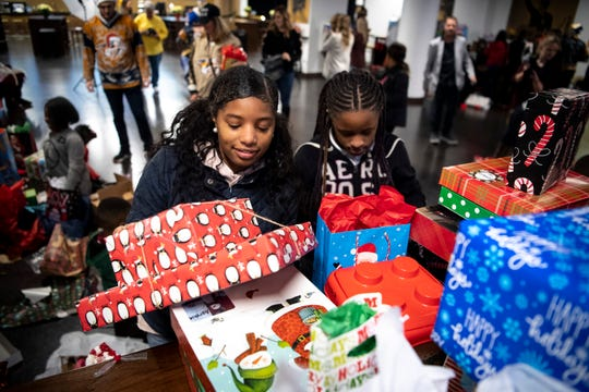 Sherriece Harvell, left, 17, and Miracle Robertson, right, 12, pick up their gifts and during the West Nashville Dream Center Holiday Party at Bridgestone Arena in Nashville, Tenn., Wednesday, Dec. 12, 2018.