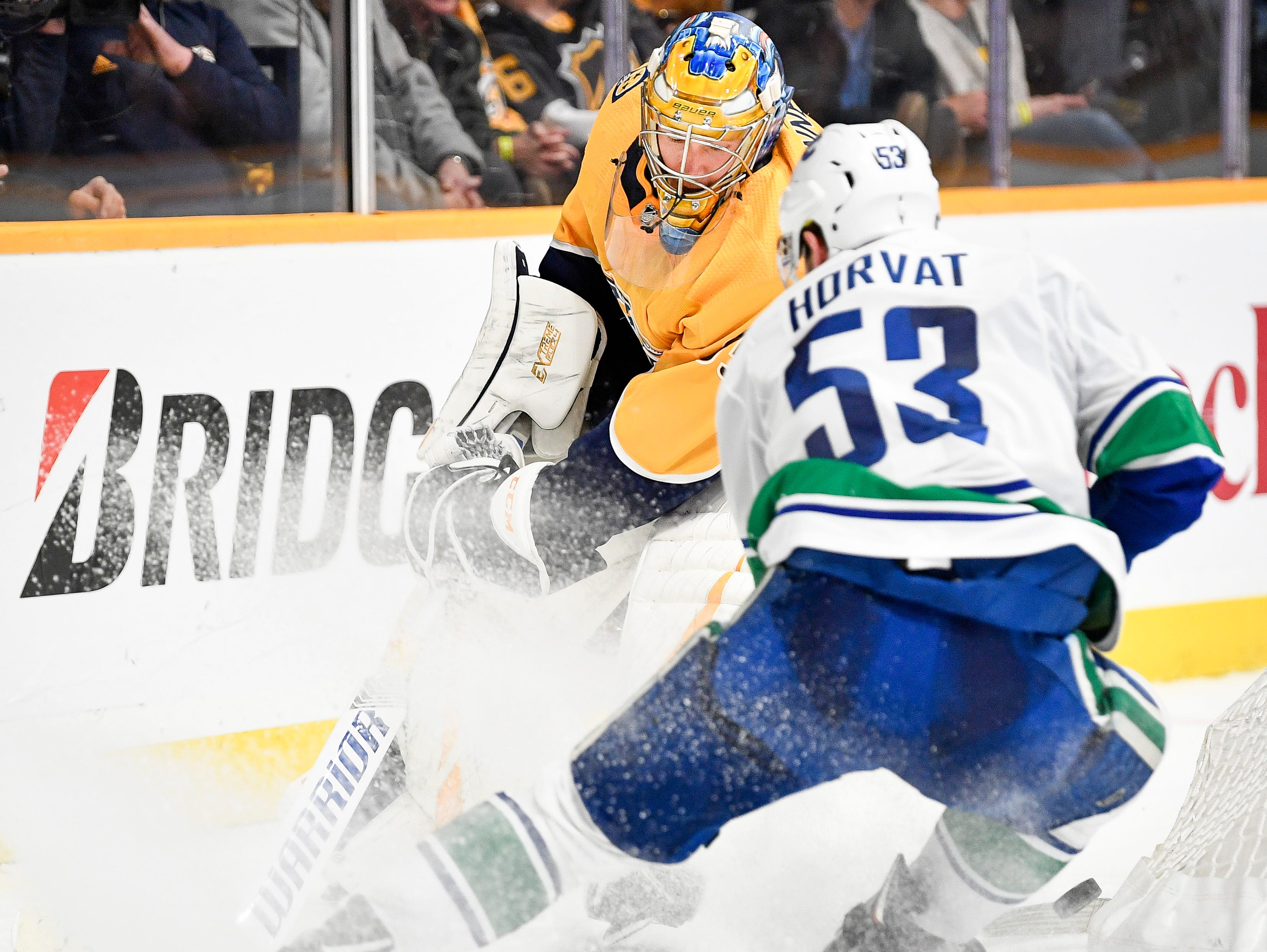 Nashville Predators goaltender Pekka Rinne (35) fights for the puck behind the net with Vancouver Canucks center Bo Horvat (53) during the second period at Bridgestone Arena in Nashville, Tenn., Thursday, Dec. 13, 2018.