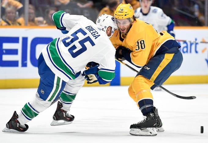 Nashville Predators right wing Ryan Hartman (38) battles for the puck with Vancouver Canucks defenseman Alex Biega (55) during the first period at Bridgestone Arena in Nashville, Tenn., Thursday, Dec. 13, 2018.