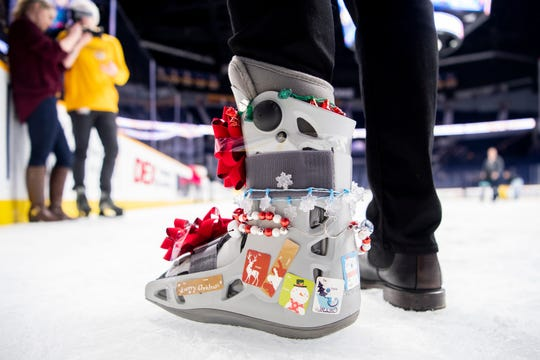 Nashville Predators left wing Austin Watson wears holiday decorations on his boot during the West Nashville Dream Center Holiday Party at Bridgestone Arena in Nashville, Tenn., Wednesday, Dec. 12, 2018.