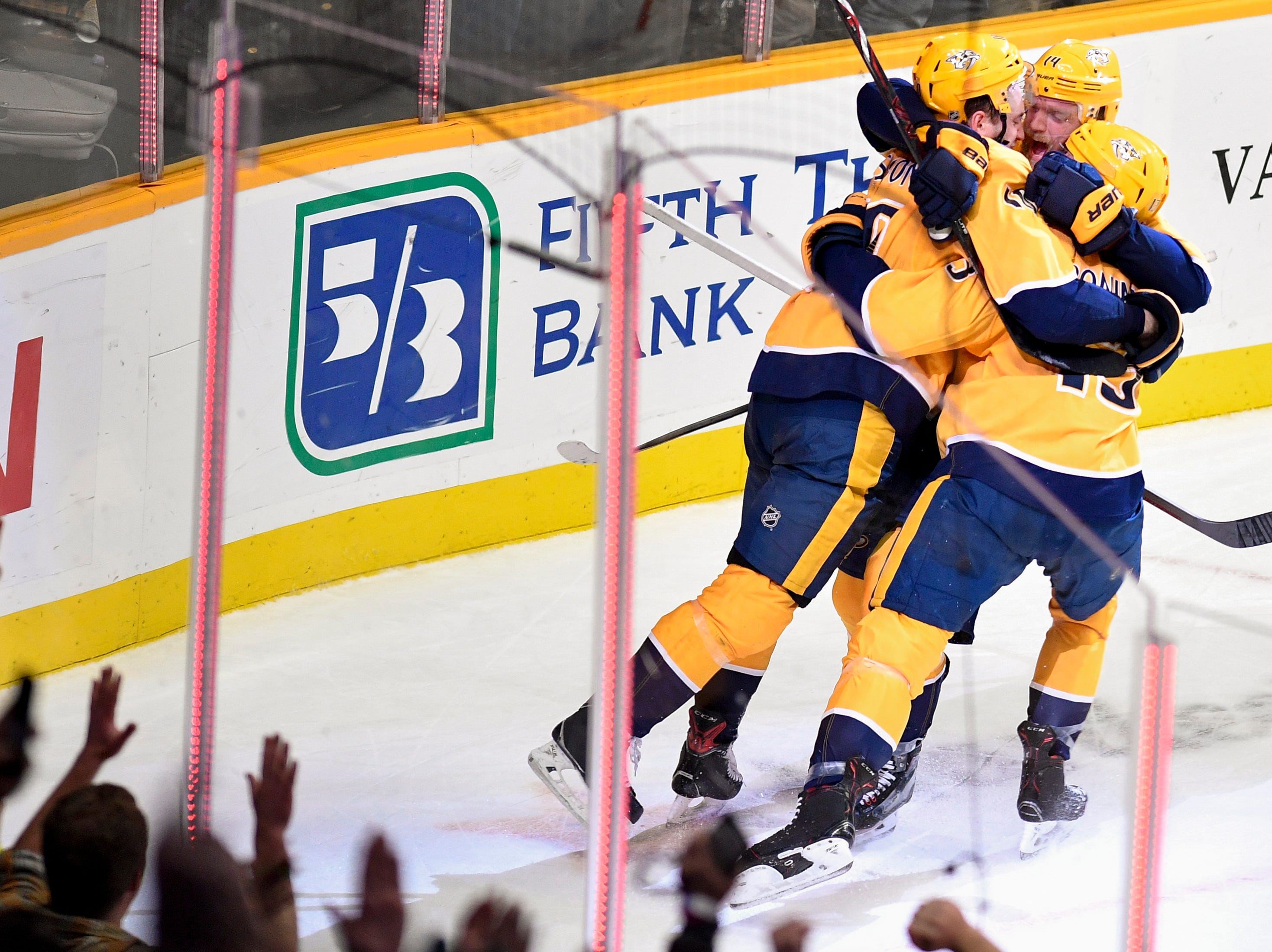 Nashville Predators center Colton Sissons (10) celebrates his game-winning goal against the Vancouver Canucks with defenseman Mattias Ekholm (14) and center Nick Bonino (13) in overtime at Bridgestone Arena in Nashville, Tenn., Thursday, Dec. 13, 2018.