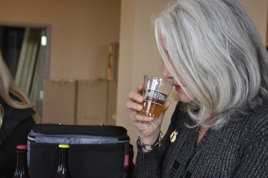 Trish Nelson tastes a beer from Delaware-based Dogfish Head Brewery. She and husband John Nelson plan to offer Dogfish Head Brewery's beer at Flytes Brewhouse in Pleasant View.