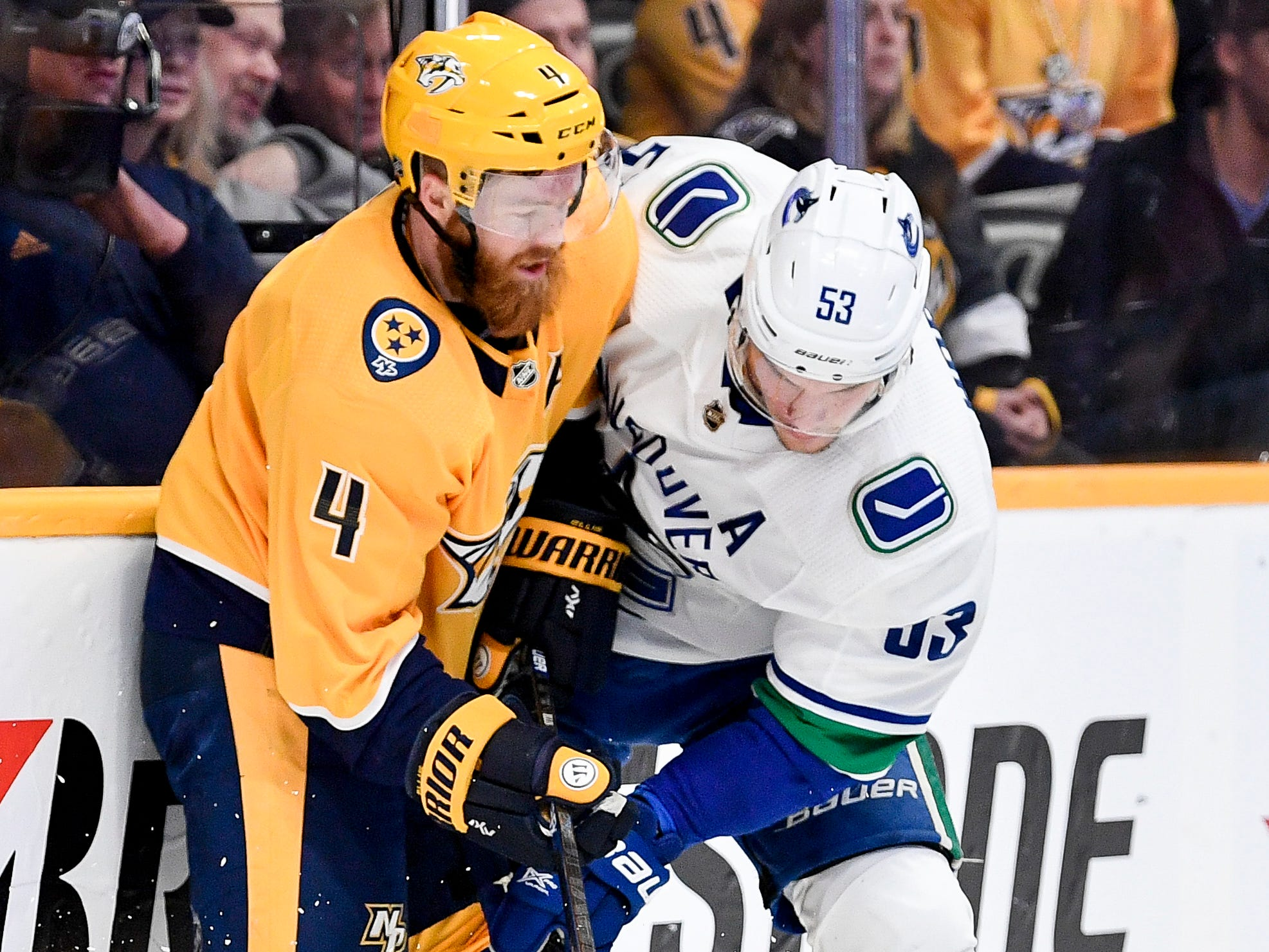 Nashville Predators defenseman Ryan Ellis (4) fights for the puck with Vancouver Canucks center Bo Horvat (53) during the first period at Bridgestone Arena in Nashville, Tenn., Thursday, Dec. 13, 2018.