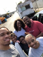 Vanderbilt football player LaDarius Wiley, front left, his mother Sue, front right, and members of their family pose for a photo after serving food to more than 100 homeless people the morning after funeral for Lincoln Wiley Sr., LaDarius' dad.