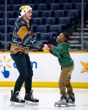 Nashville Predators center Colton Sissons helps Andre Odom, 7, learn to skate during the West Nashville Dream Center Holiday Party at Bridgestone Arena in Nashville, Tenn., Wednesday, Dec. 12, 2018.