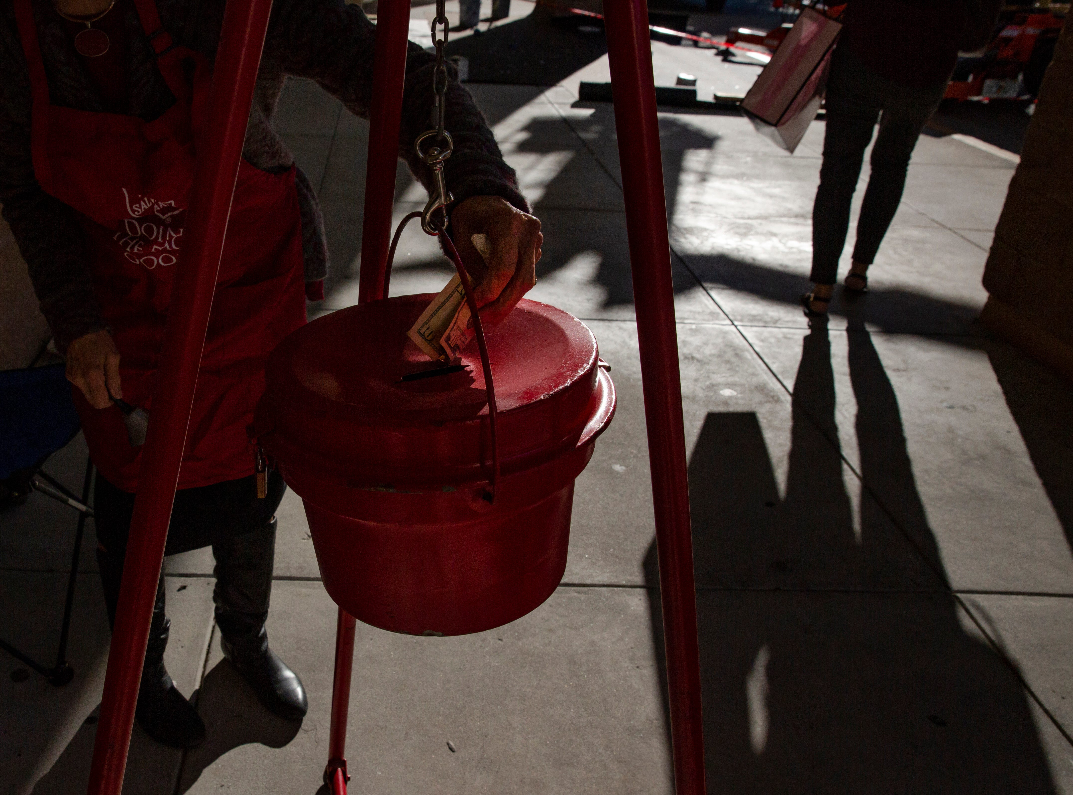 Daily News reporter Harriet Heithaus places a $10 bill in the Salvation Army kettle, after it was handed to her by a stranger exiting Coastland Center mall  on Nov. 28.