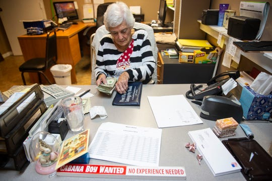 Evelyn Dickerson puts away money that she counted on Wednesday, Dec. 12, 2018, at Wynn's Market in Naples. She says it was her co-workers who put the sign on her desk advertising an open position for a cabana boy, but admits she's had quite a few applicants.