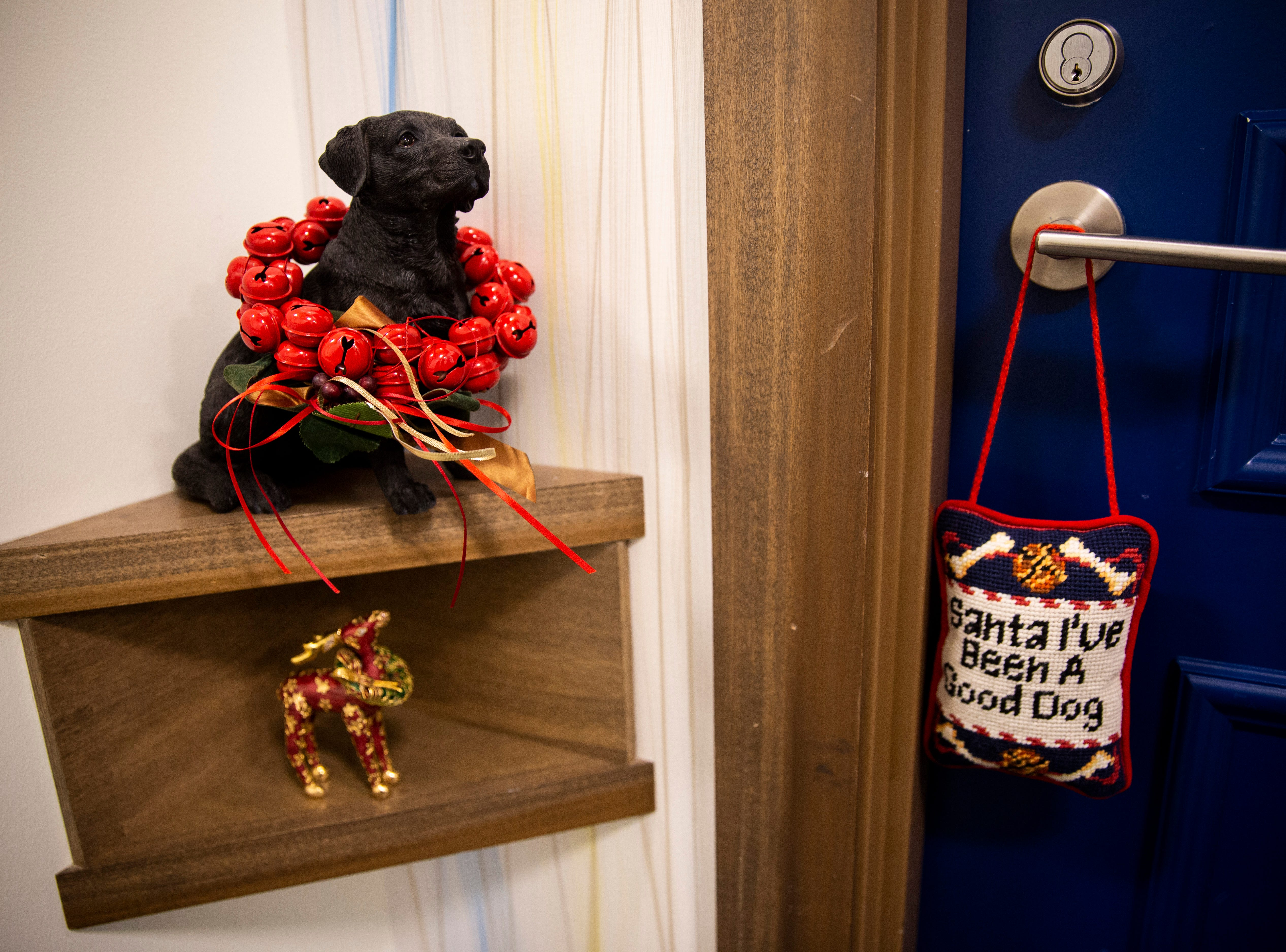 Christmas decorations and a statue resembling Lynn Hertel's service dog, Dutch, decorate the entryway of the apartment Hertel shares with her father on Tuesday, Dec. 11, 2018, in North Naples.