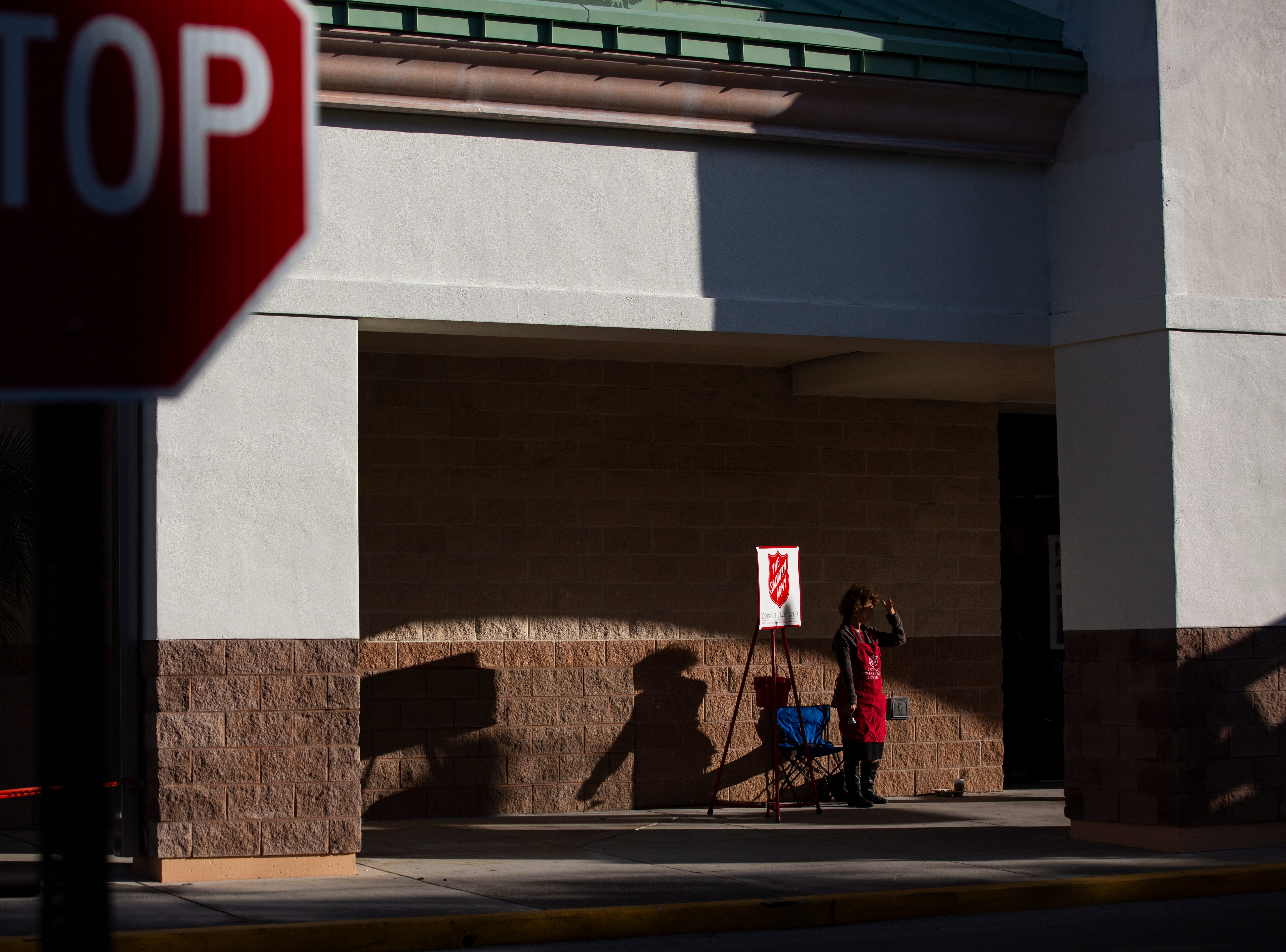 Harriet Heithaus, a reporter from the Naples Daily News, shades her face from the sun as she waits to ring the bell for Salvation Army at Coastland Center near the back entrance of J.C. Penney on Nov. 28.