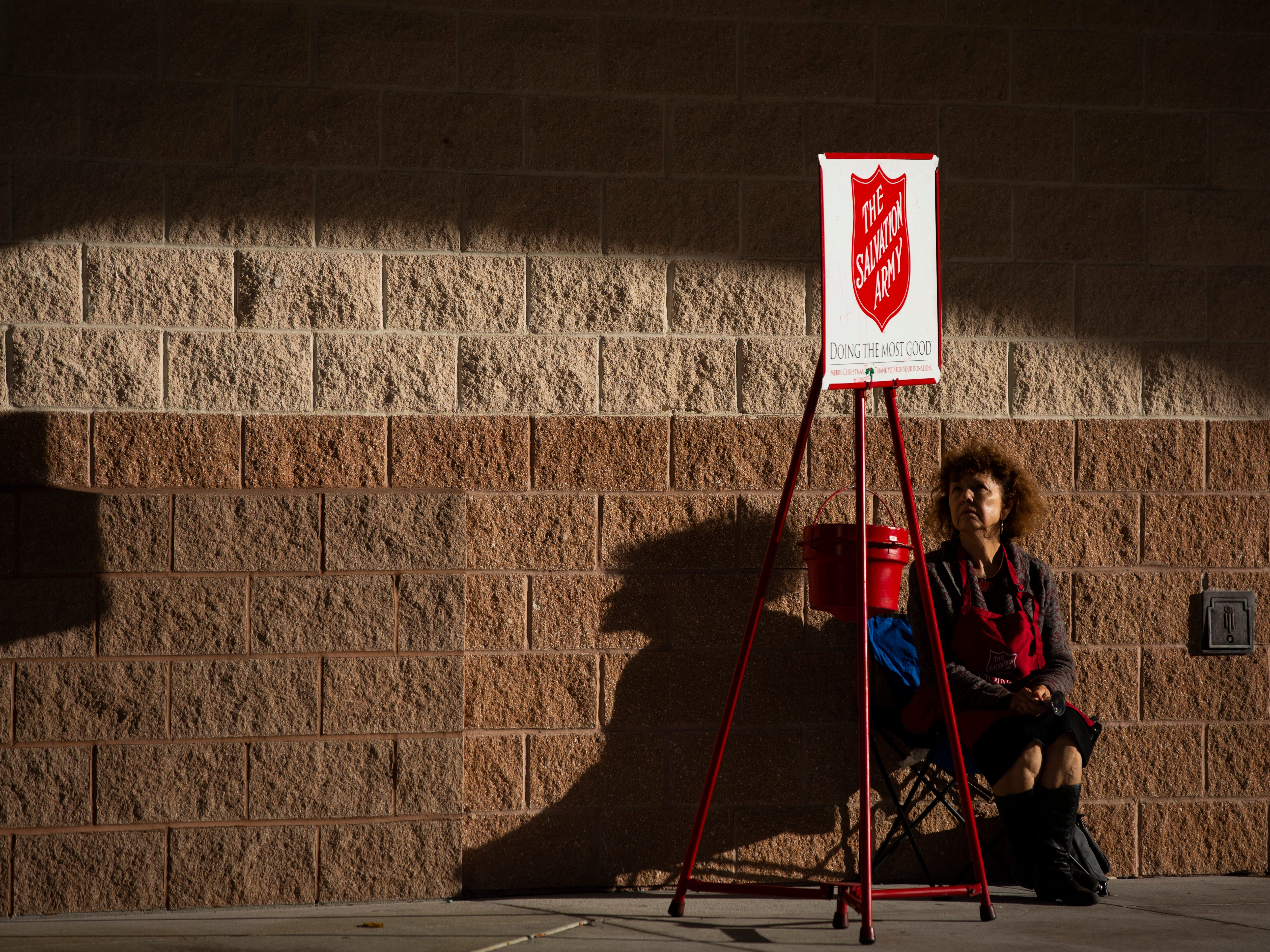 Harriet Heithaus, a reporter from the Naples Daily News, reads the Salvation Army volunteer rules, as she waits to ring the bell at Coastland Center on Nov. 28, 2018.