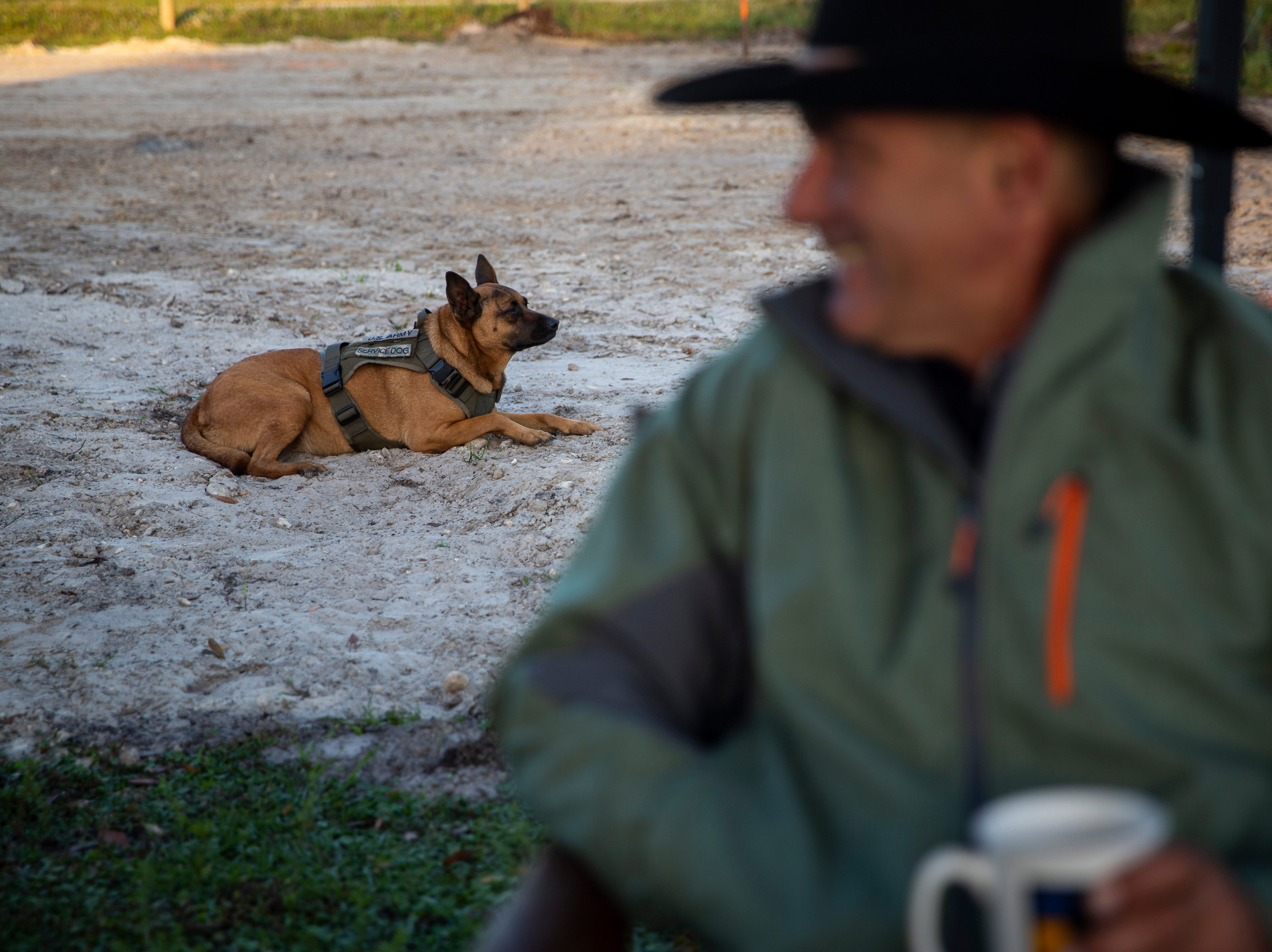 Steven DePalma drinks his morning coffee while his service dog, Mia, lies close by in the dirt where DePalma plans to build a barn on Friday, December 7, 2018, at his ranch in Fort Myers.