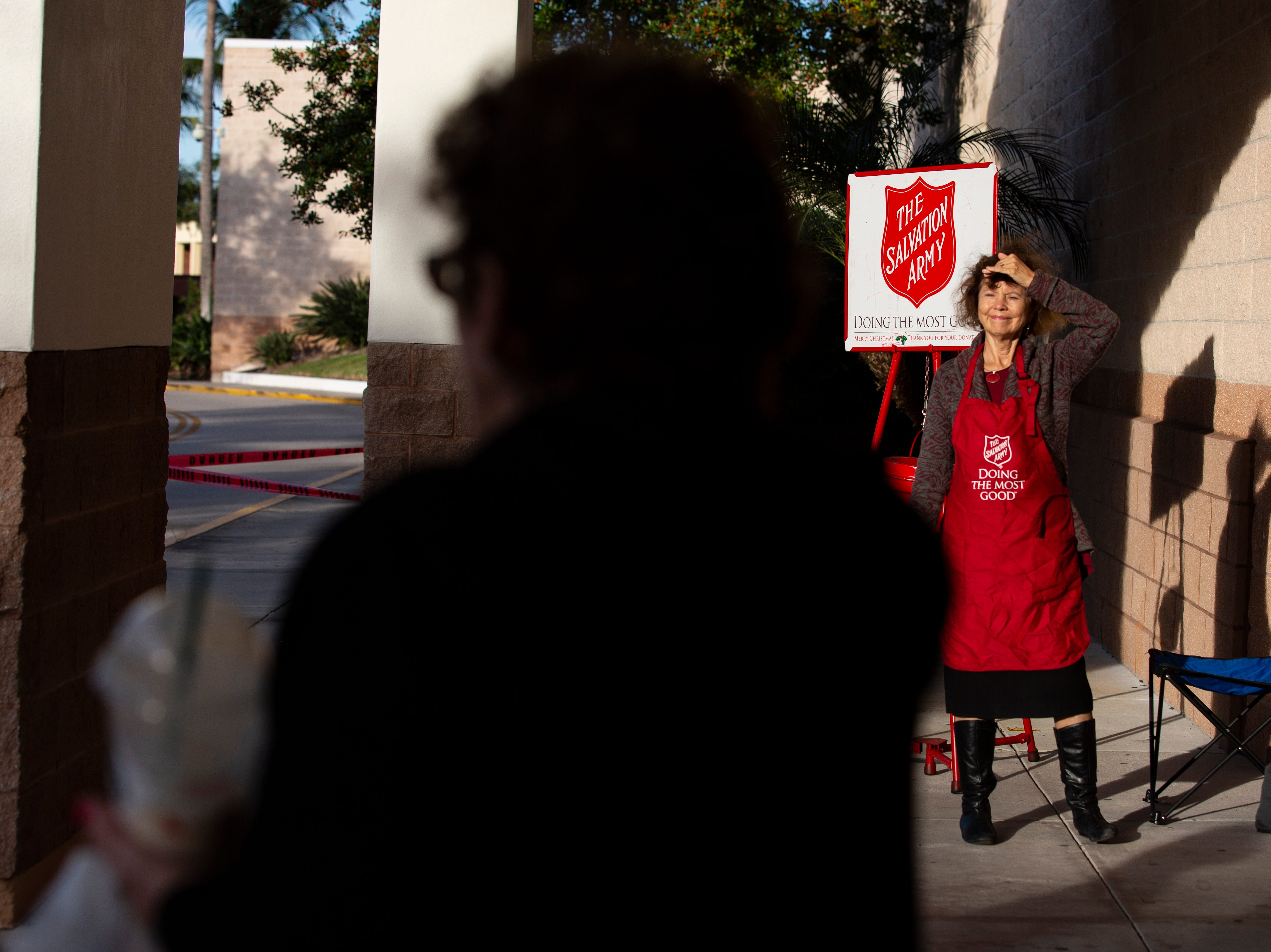 With a smile on her face, Daily News reporter Harriet Heithaus rings the bell for a passerby, who walks away without looking at her, Nov. 28 at Coastland Center mall.