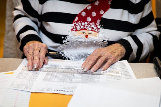 Evelyn Dickerson works on the accounts on Wednesday, Dec. 12, 2018, at Wynn's Market in Naples. She says she has a different Christmas sweater for every day in December, and her co-workers look forward to seeing which one she'll wear each day.