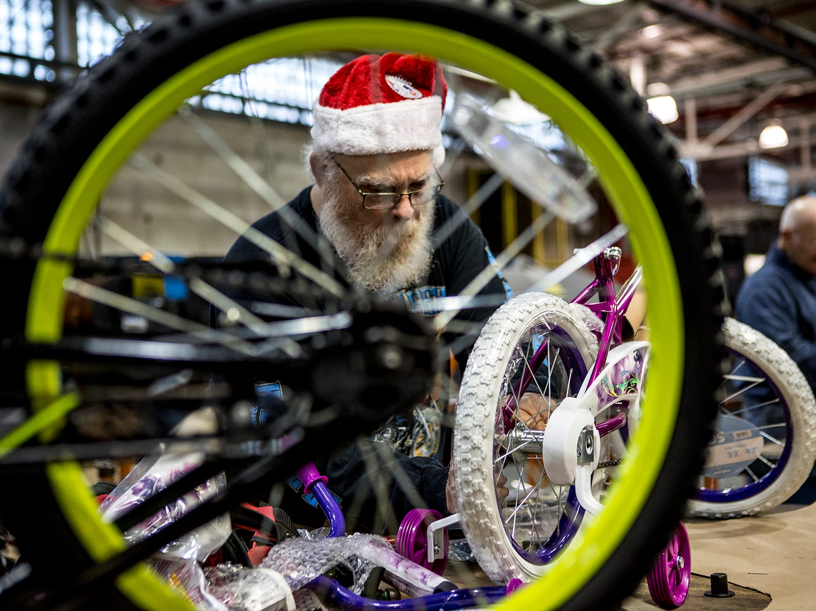 Larry Sceurman wears his Santa hat while putting together bikes at Owens Corning. For the fourteenth year workers at Owens Corning put together bikes for kids in need to be given out at the Salvation Army's toy drive later this month. This year 138 bikes were assembled by Owens Corning and Aboris.
