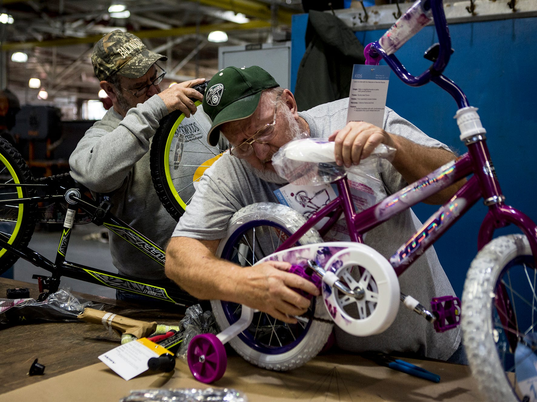 Ronnie Combs and Pete Becker work on assembling bikes Friday at Owens Corning. For the fourteenth year workers at Owens Corning put together bikes for kids in need to be given out at the Salvation Army's toy drive later this month. This year 138 bikes were assembled by Owens Corning and Aboris.