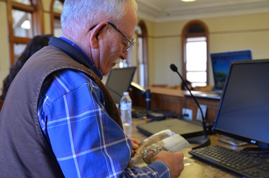 Luna County Commissioner member John Sweetser looks over presented pictures of the aftereffect of Randy Pirie's property.