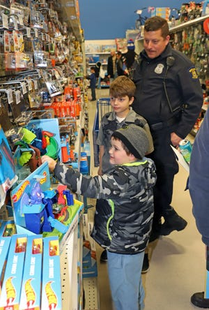 Westland Officer Kevin Yudt shops with two boys during the Dec. 11 Shop With a Hero event at the Meijer store in Westland.