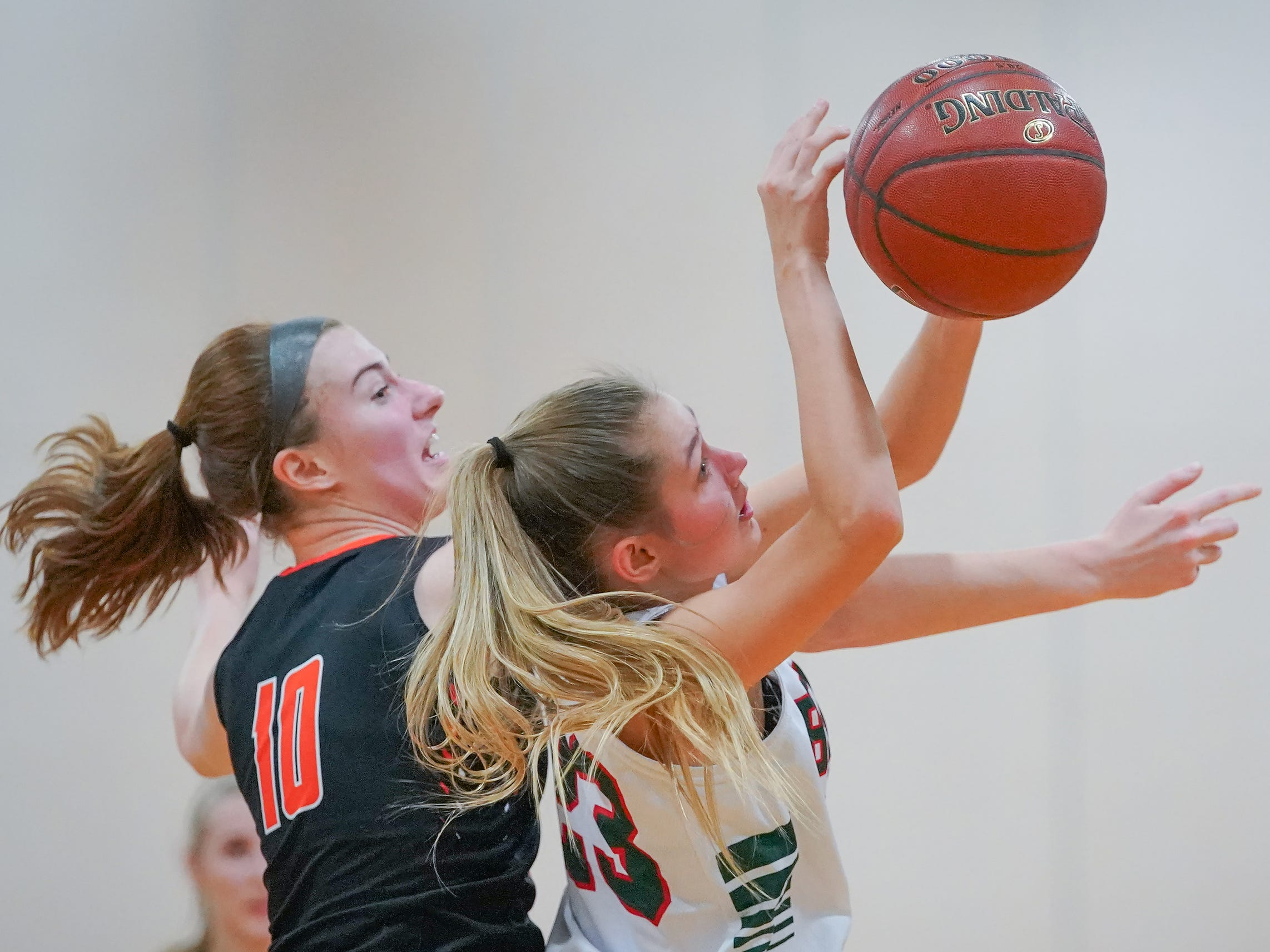 Hana Goeser (10) of Plymouth battles with Emily Klawitter (23) of Berlin for a rebound. The Berlin Indians hosted the Plymouth Panthers in an East Central Conference basketball game Thursday evening, December 13, 2018.