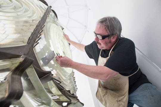 Kurt Fosburg, owner of Superior Lighthouse Restoration, marks the parts of the Fresnel lens that need to be ground before installing it Friday at the Pensacola Lighthouse.